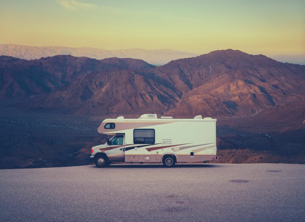 rv parked in front of desert mountains