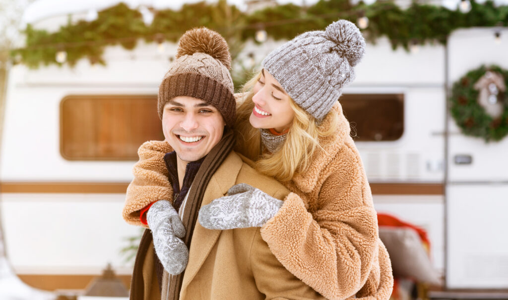 how to winterize your rv - couple in winter clothes in front of trailer